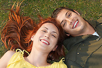 Young couple lying on grass portrait overhead view