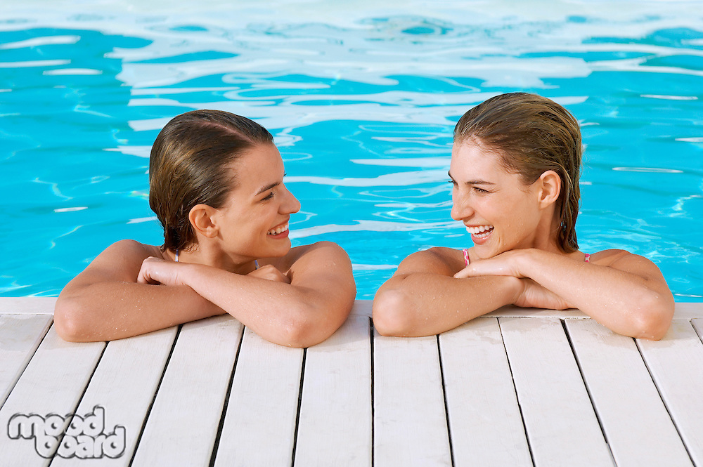 Two young women in pool at poolside talking front view