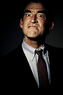 Low angle, close up, head and shoulders view of a mature man in a business suit with a angry expression on his face.  Studio shot against a dark background. (releasecode: jk_mr1025) (Model Released)