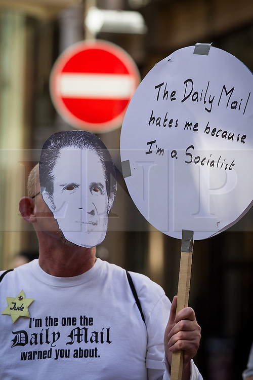 """© Licensed to London News Pictures . 06/10/2013 . Manchester , UK . A man wearing a Ralph Miliband face mask , a gold star with """" Jude """" written on it , a t-shirt that reads """" I'm the one the Daily Mail warned you about """" and carrying a placard that reads """" The Daily Mail hates me because I'm a Socialist """" . A demonstration against the Daily Mail newspaper in central Manchester's St Anne's Square today (6th October 2013) . Photo credit : Joel Goodman/LNP"""
