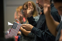 A U.S. citizen applicant holds an American flag as he takes the pledge to become a U.S. citizen during a naturalization ceremony at the Evo A. DeConcini U.S. Courthouse in Tucson, Arizona, U.S., on Friday, Sept. 16, 2016. Photographer: David Paul Morris/Bloomberg