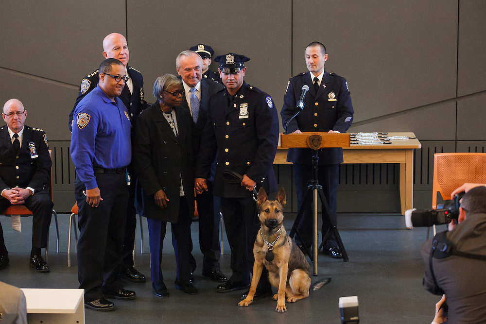 Police Officer Manuel Checo with Canine Omar, honoring Detective Omar Edwards of PSA 5, with family members of Mr. Edwards, during the NYPD Transit Bureau Canine Unit Graduation Ceremony at the College Point Police Academy in Queens, NY on Tuesday, Oct. 6, 2015.<br /> <br /> Andrew Hinderaker for The Wall Street Journal<br /> NYSTANDALONE