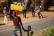 A woman and her child walk along a road to go fetch water at a spontaneous settlement where they now live after their home was destroyed by floods in the village of Kpoto, Benin on Wednesday October 27, 2010.