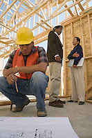 Two architects talking and construction worker looking at blueprints