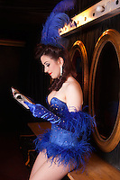 Showgirl reading newspaper