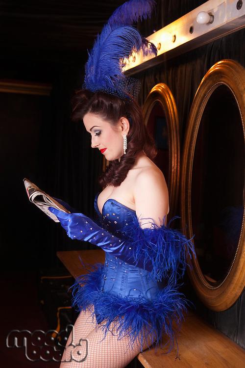 Showgirl reading newspaper