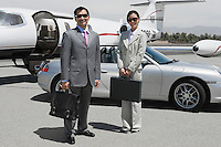 Portrait of mid-adult businesswoman and mid-adult businessman standing in front of private plane on landing strip.