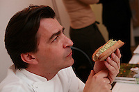Chef Yannick Alleno of the restaurant le Meurice - eating a hotdog Tete de Veau- - photograph by Owen Franken for the NY Times..February 9, 2012..