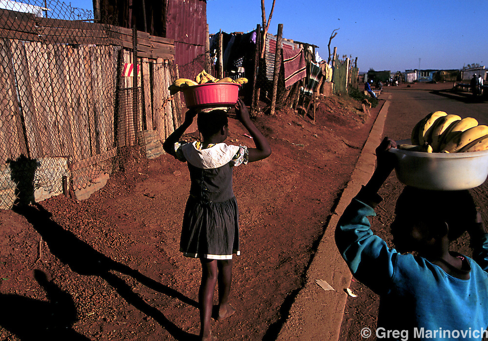IPMG0335 South Africa, Bekkersdal, 1995: Young girls carry bananas for sale in Bekkersdal township west of Johannesburg, 1995. Child labour is common in the townships, where children help the family make ends meet..Photograph by Greg Marinovich/South Photographs