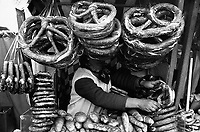 October 1974, Munich, Germany --- A street vendor is almost covered in pretzels and loaves of bread at a food booth at Oktoberfest in Munich, Germany. --- Image by © Owen Franken/CORBIS
