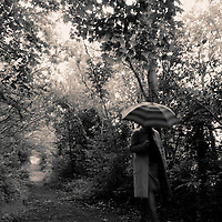 woman walking through woods in the rain