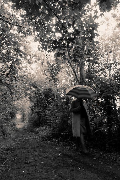 woman walking through woods in the rain