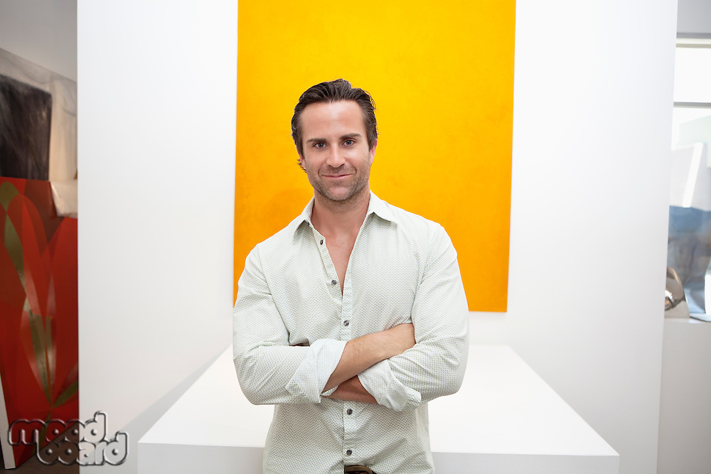 Half-length portrait of smiling young man in front of yellow painting