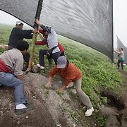 """La comunità di SMT, ha ricevuto una donazione da parte di una azienda locale: con questi soldi hanno comprato i materiali per costruire 10 """"atrapanieblas"""". La domenica, unico giorno di pausa per la maggior parte di loro, si riuniscono e , sotto la direzione di Jorge dell'associazione """"peruanos sin aguas"""", innalzano questi teli di 4x6 metri."""