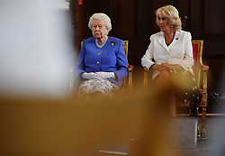 Queen Elizabeth II and the Duchess of Cornwall watch a demonstration of a dog from the charity Medical Detection Dogs sniffing out bladder cancer during the 10th anniversary celebration of the charity at the Royal Mews, in London.