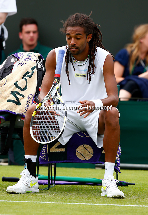 Wimbledon Championships 2013, AELTC,London,<br /> ITF Grand Slam Tennis Tournament,<br /> Dustin Brown (GER) sitzt auf seinem Stuhl in der Spielpause und flippt <br /> seinen Schlaeger,Einzelbild,Ganzkoerper,Hochformat,