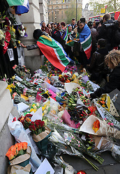 Mourners draped in South African flags leave flowers outside  South Africa House in London, Friday, 6th December 2013, following the death Nelson Mandela, Picture by Stephen Lock / i-Images