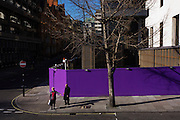 Against a purple construction site hoarding, passers-by simultaneously walk through an incongruous city landscape.