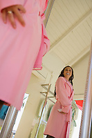 Young Woman Trying on Pink Trench Coat