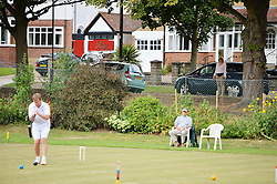 © Licensed to London News Pictures. 14/08/2013. Surbiton, UK. A lady with dog watches from the road. People participate in the14th World Association Croquet Championship at the Surbiton Croquet Club, Kingston upon Thames on the 14th August 2013. The Final will be played on Sunday 18th August. 80 competitors from 20 countries are taking part. Photo credit : Mike King/LNP