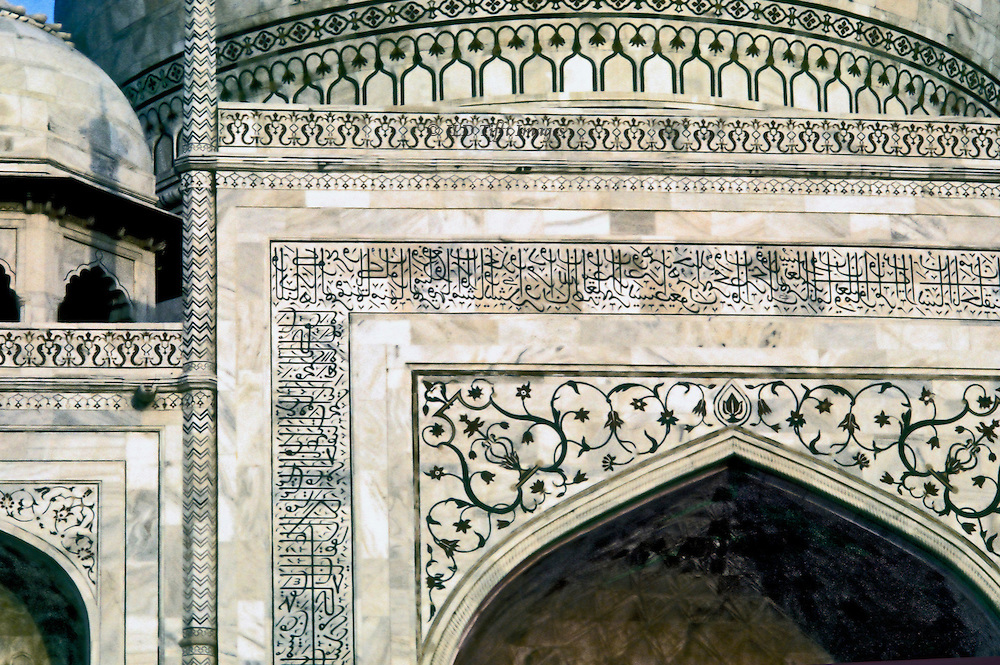 Detail of inscription bands, foliate scrollwork, and other detailed pietra dura ornament on the upper facade of the Taj Mahal.