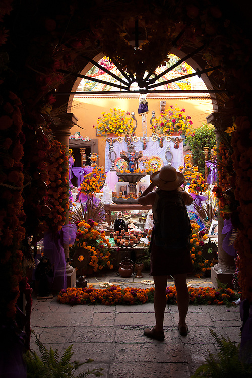 North America, Mexico, San Miguel de Allende, woman under arch takinig photos of altar at Day of the Dead celebration, also known as Dios de los Muertos.  Mexicans celebrate the Day of the Dead on November 1st and 2nd in connection with the Catholic holy days of All Saints' Day and All Souls' Day.  MR, PR