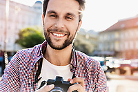 Portrait of Smiling Young attractive man holding camera with lens flare in background