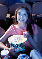 Smiling young woman Eating Popcorn watching movie in Theatre