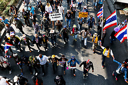 © Licensed to London News Pictures. 20/01/2014. Anti-Government protestors lock arms and march in an attempt to shutdown the Government Savings Bank in Bangkok Thailand. Anti-government protesters launch 'Bangkok Shutdown', blocking major intersections in the heart of the capital, as part of their bid to oust the government of Prime Minister Yingluck Shinawatra ahead of elections scheduled to take place on February 2. Photo credit : Asanka Brendon Ratnayake/LNP