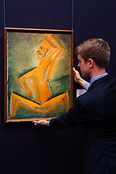 "London, November 7th 2014. Sotheby's is to hold its Inaugural 20TH Century Art– A Different Perspective sale on November 12th in London, where collectors will have the opportunity to acquire some highly regarded examples of avante-garde and abstract art. PICTURED: Sotheby's European Paintings specialist Richard Lowkes  adjusts the hanging of ""Cubist Figure"" by Otakar Kubin, an important rediscovery from the artist's cubist period. with an estimated value of up to £120,000."