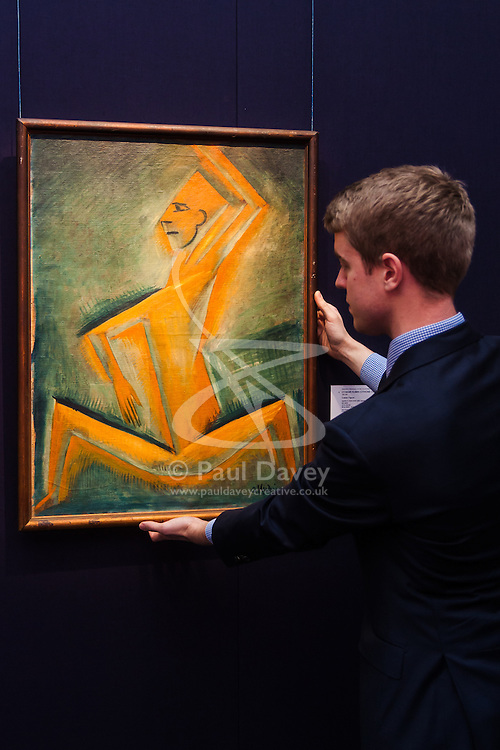 """London, November 7th 2014. Sotheby's is to hold its Inaugural 20TH Century Art– A Different Perspective sale on November 12th in London, where collectors will have the opportunity to acquire some highly regarded examples of avante-garde and abstract art. PICTURED: Sotheby's European Paintings specialist Richard Lowkes  adjusts the hanging of """"Cubist Figure"""" by Otakar Kubin, an important rediscovery from the artist's cubist period. with an estimated value of up to £120,000."""