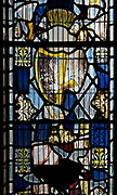Fragments of medieval stained glass window   showing a harp being played inside the church at South Elmham All Saints, Suffolk, England, UK