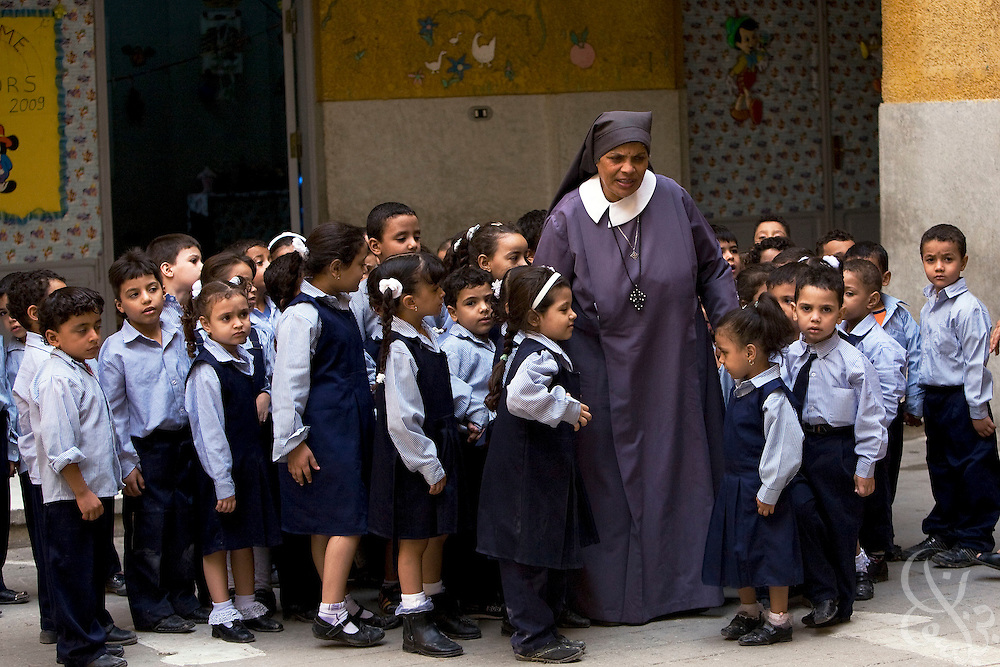 Sister Sara walks with children at the school for poor children  that she helped found more than 30 years ago with the famous French nun, Sister Emanuel in the Manshiyet Nasser district of the Egyptian capital, Cairo October 16, 2008. The school now provides an education to more than 1200 students from the surrounding slums which are a large garbage collection district.
