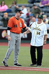 09 July 2015: Pete Rose know affectionately to fans as Charlie Hustle the current Major League Baseball all time hits leader exits the CornBelters dugout as manager for the night to take his place in the first base coaches box shakes hands and makes some small talk with Boomers 1st baseman Willi Martin. Pete Rose night during a Frontier League Baseball game between the Schaumburg Boomers and the Normal CornBelters at Corn Crib Stadium on the campus of Heartland Community College in Normal Illinois
