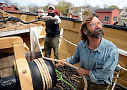 Rigger Tim Reilly and lead rigger Matt Otto watch for a signal from rigger Alex Peacock atop the mizzen mast as they use the ship's windlass to raise the mizzen topmast on the whaleship Charles W. Morgan Wednesday, May 7, 2014 at the Mystic Seaport's H.B. duPont Preservation Shipyard. The Morgan, the last remaining wooden whaling ship remaining and the oldest American commercial vessel still in existence as well as a National Historic Landmark, was re-launched in July of 2013 and will embark on its 38th voyage, a tour of historic New England ports, this summer.  (Sean D. Elliot/The Day)
