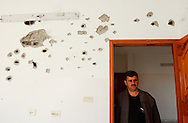 """Gaza Strip, Palestine, December 2008. Akram Ghoniem inspects his sister's  house, which was destroyed during an Israeli Army operation known as Operation Cast Lead. """"The Israelis kept 47 members of my family, including two disabled children, in one room for two days without food and water and then kicked us out in order to accommodate more troops,"""" he said. The conflict resulted in between 1,166 and 1,417 Palestinian and 13 Israeli deaths (4 from friendly fire).     (PHOTO: MIGUEL JUAREZ LUGO)"""