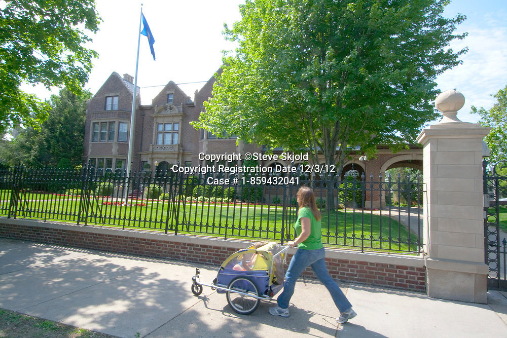 Woman age 30 pushing her two children in a stroller in front of Governor's Residence Mansion. St Paul Minnesota MN USA