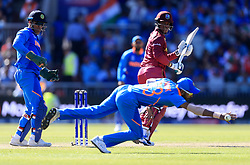 India's Hardik Pandya dives at a ball from West Indies' Shimron Hetmyer during the ICC Cricket World Cup group stage match at Emirates Old Trafford, Manchester.