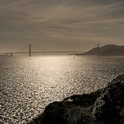 A view of the Golden Gate Bridge, silhouetted in the afternoon sun, as seen from Alcatraz Island in San Francisco Bay.