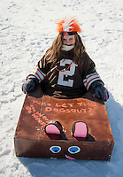 """Kendall Myers crossed the finish line in her Cleveland Browns """"Who Let the Dogs Out"""" sled during Gilford Parks and Recreation Cardboard Derby on Wednesday morning.  (Karen Bobotas/for the Laconia Daily Sun)"""