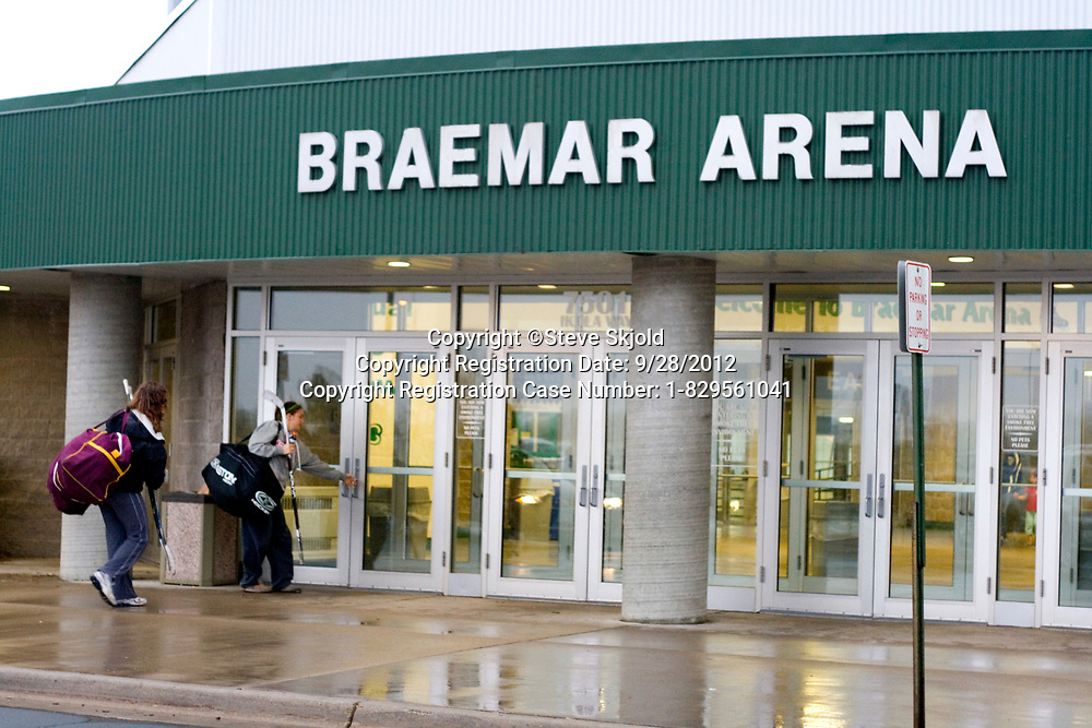 Teen women hockey players entering Braemar Arena for a game. Edina Minnesota MN USA