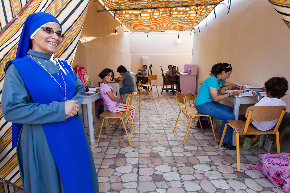 A nun at the Anjara Orphanage in Jordan proudly shows the room where girls are tutor by local young women.