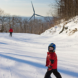 A young skier near the wind turbine at Jiminy Peak ski resort in the Berkshire Mountains in Hancock, Massachusetts.