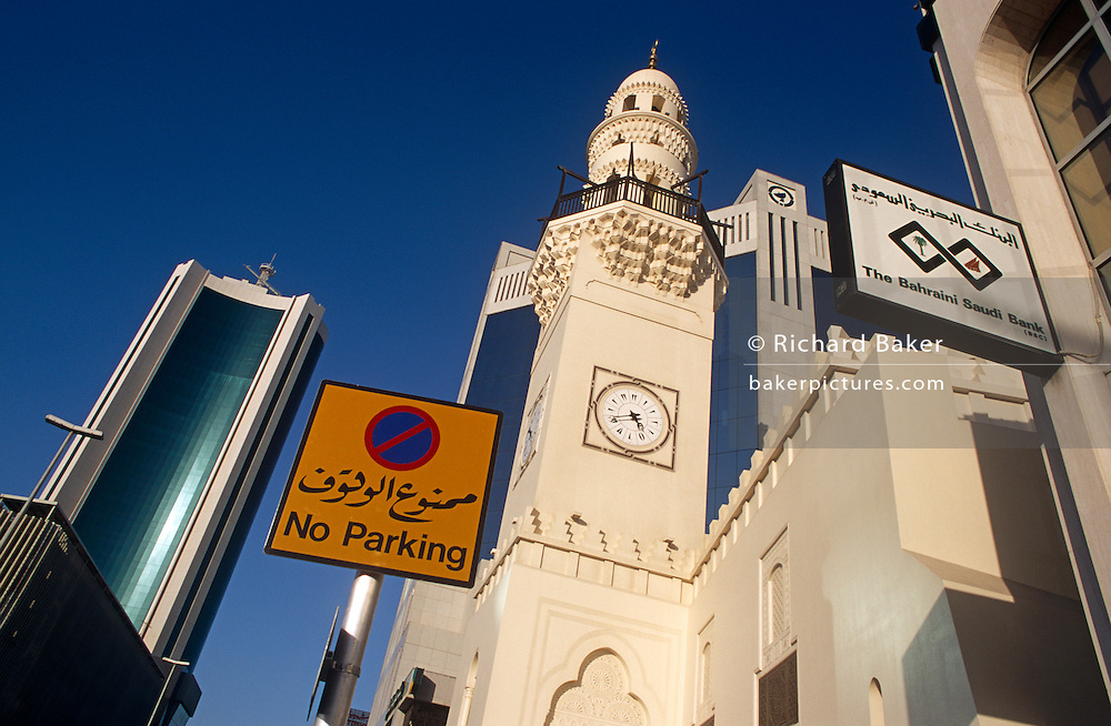 Modern architecture of bank buildings and an older minaret tower seen in Manama City in the Gulf state of Bahrain