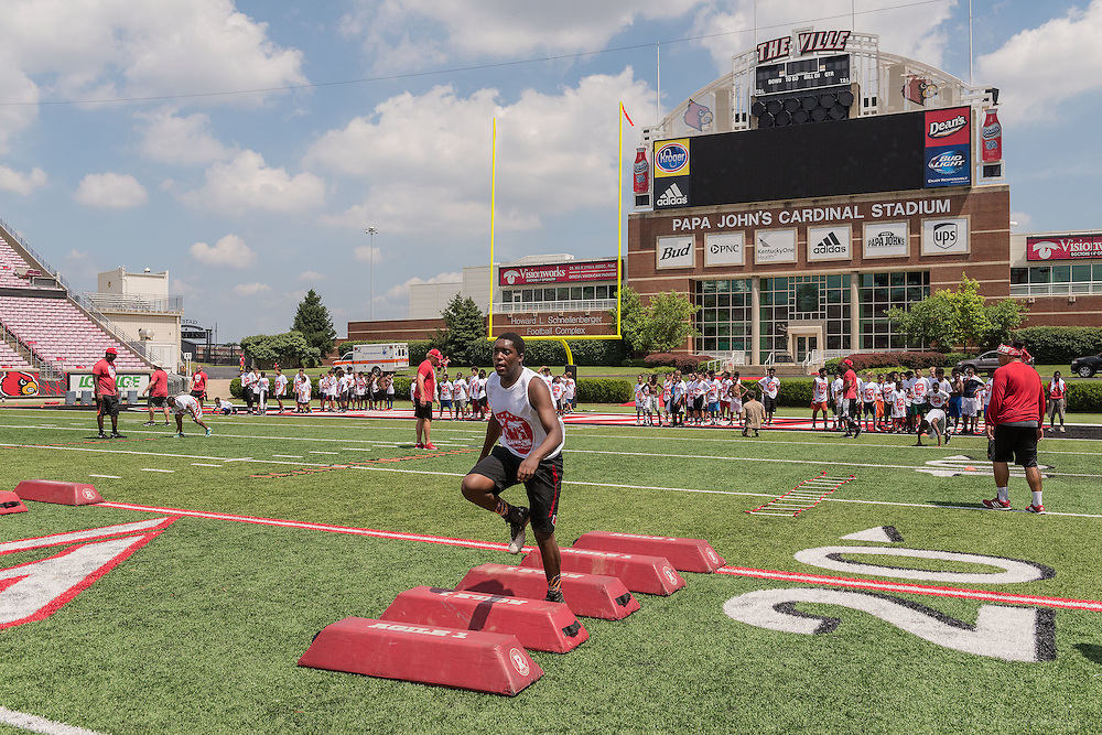 William Phillips, 14, an Atherton sophomore and  quarterback on their football team, runs a drill during the American Football Without Barriers youth football camp at the University of Louisville's Papa John's Cardinal Stadium. June 25, 2016