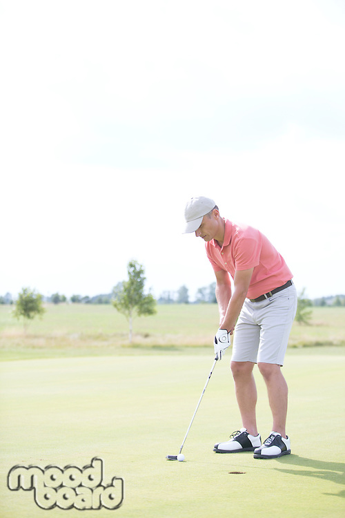 Full-length of middle-aged man playing golf at course