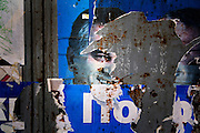 Street life in the Serbian section of (Kosovska) Mitrovica. Torn political poster for the Serbian Radical party.