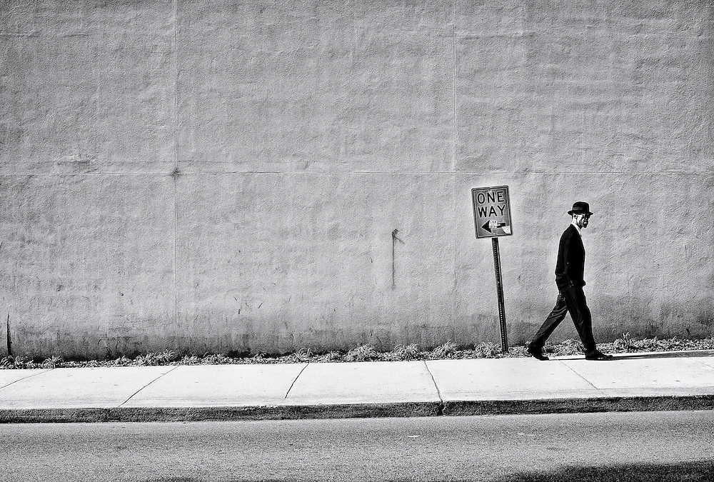 Man in a suit and hat walking past a one way sign on a sidewalk in an urban environment.