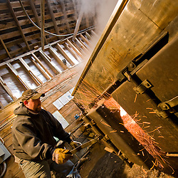 Ralph Luce stoking the fire in the sap evaporator in his sugar house  at Sugarbush Farm in Woodstock, Vermont.