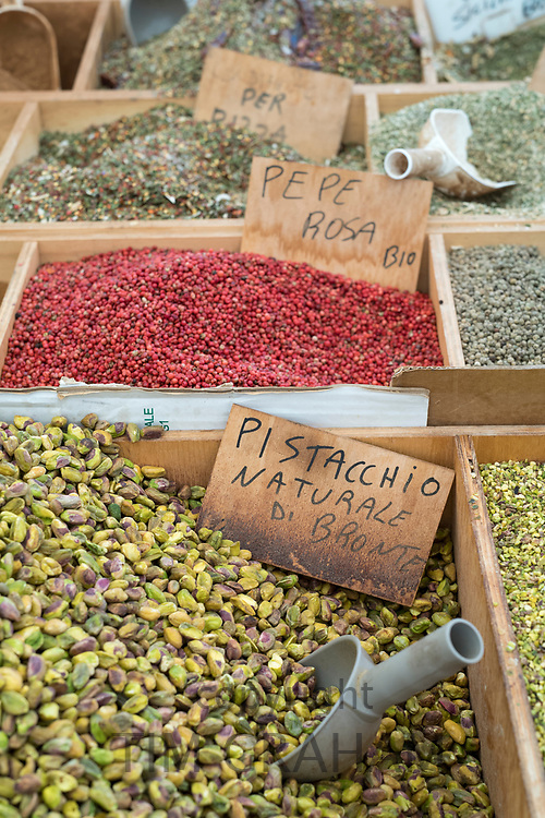 Dried goods, pepper and pistachio nuts on display for sale on market stall at old street market - Mercado -  in Ortigia, Syracuse, Sicily